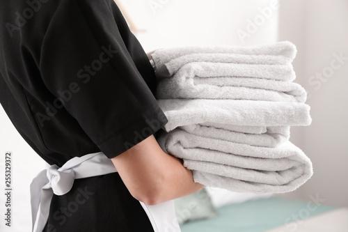 Beautiful female housekeeper with clean towels, closeup