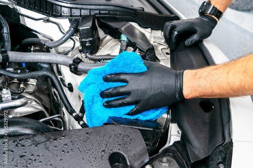 Fototapeta A man cleaning car engine with microfiber cloth. Car detailing or valeting concept. Selective focus. Car detailing. Cleaning with sponge. Worker cleaning. Car wash concept solution to clean obraz