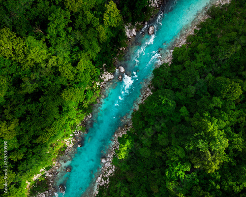 Blue river flowing in forest at spring