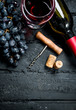Wine background. Red wine with grapes and corkscrew.