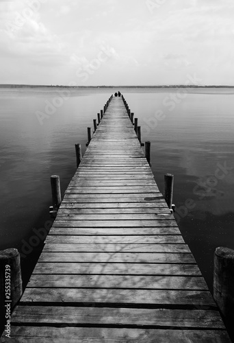 Cuadros en Lienzo Wooden pier at silence lake, monochrome shoot