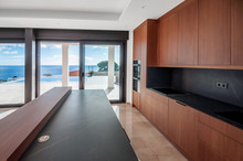 Luxurious Wooden Kitchen Overlooking The Sea.  Modern Kitchen With An Island.