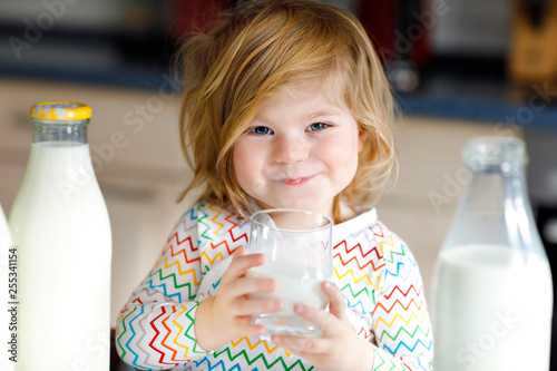 Fototapeta Adorable toddler girl drinking cow milk for breakfast. Cute baby daughter with lots of bottles. Healthy child having milk as health calcium source. Kid at home or nursery in the morning. obraz