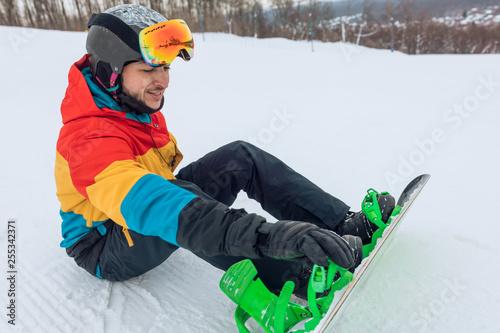 Fotografia  handsome positive man preparing for snowboarding, side view full length photo
