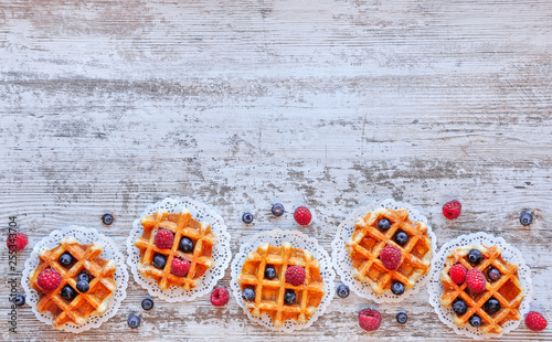 Valokuva  Traditional waffles with fresh  raspberries and blueberries on lace doily on wooden background
