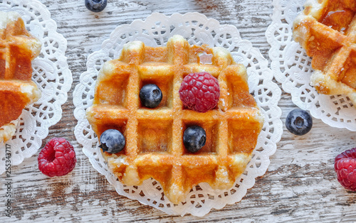 Traditional waffles with fresh  raspberries and blueberries on lace doily on wooden background Canvas-taulu