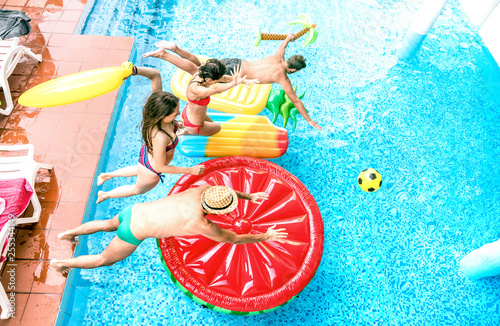 High angle view of millenial friends jumping at swimming pool party - Youth vaca Canvas Print