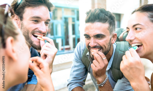 Valokuvatapetti Happy millenial friends having fun at city center eating sugar candies - Z gener