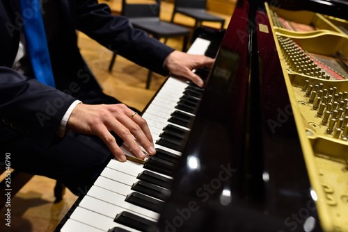 Male pianist playing classical music on a grand piano. - 255346790
