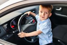 Little Blond Boy In Blue Shirt Driving A Big Car Shows Tongue