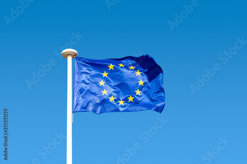 Fotografie, Obraz  European flag (a circle of twelve five-pointed yellow stars on a blue field) flying in the wind at full mast on a white pole against blue sky