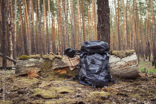 Fotografiet Tourist backpack and headphones in the forest