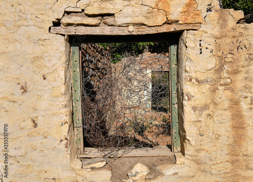 Fotografie, Obraz  Central empty green window frame on rocky wall of abandoned house