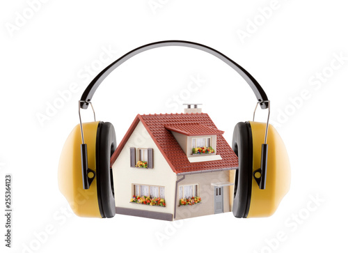 Obraz Protection against noise. Hearing protection yellow ear muffs with house miniature isolated on white background - fototapety do salonu