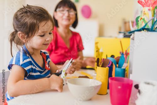 granddaughter doing handycraft together with her grandmother in nursery, improvement of fine motor skills