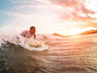 Male athlete surfing at sunset