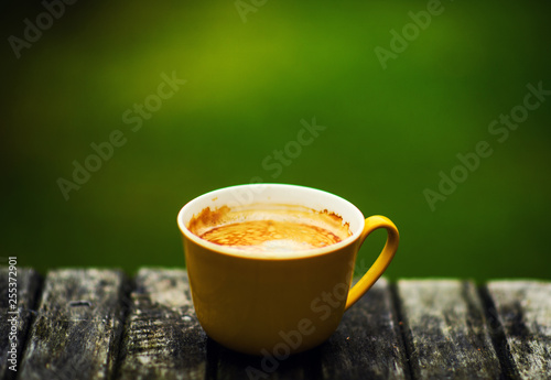 Fotografie, Obraz  A yellow cup of tasty coffee, on rustic wooden table background