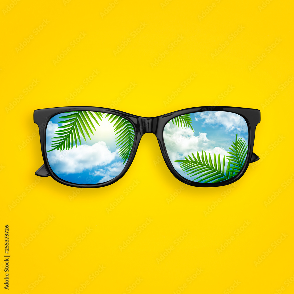 Fototapety, obrazy: Creative layout made of black sunglasses with reflected sky cloud and tropical palm leaves, on pastel yellow background. Sun glasses minimal concept flat lay. Summer concept top view