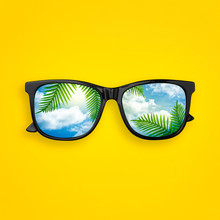 Creative Layout Made Of Black Sunglasses With Reflected Sky Cloud And Tropical Palm Leaves, On Pastel Yellow Background. Sun Glasses Minimal Concept Flat Lay. Summer Concept Top View