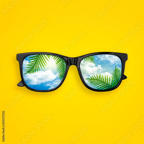 Foto  Creative layout made of black sunglasses with reflected sky cloud and tropical palm leaves, on pastel yellow background