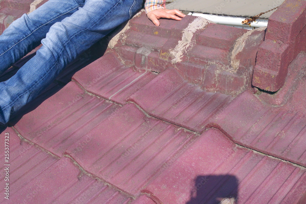 Fototapeta 男性・ボディパーツ・座る - A young man sitting alone on the Japanese traditional tiled roof