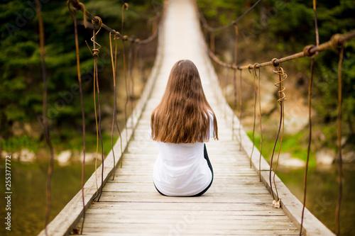 Foto  Tourist woman walk by long wooden suspension bridge above river.