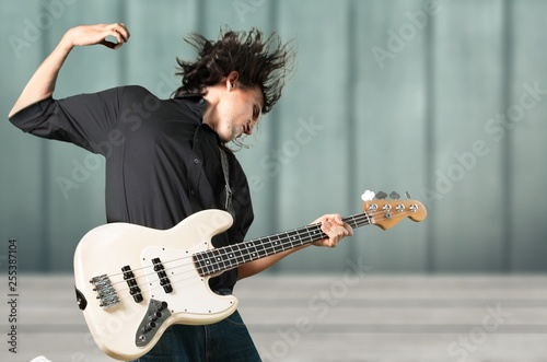 Portrait of a Musician Jumping while Playing an Electric Bass - 255387104