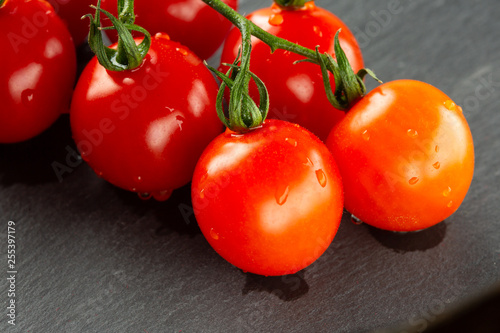 Fotografia  Wet juicy tomatoes on the branch on grey surface