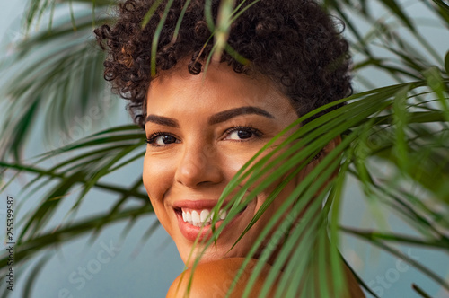Beauty young woman smiling through palm leaves Canvas
