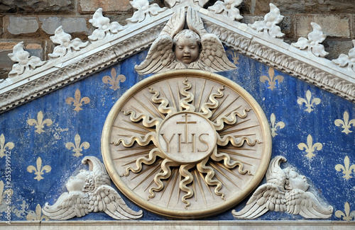 Fotografie, Obraz  Medallion with the IHS monogram between two lions, above to the entrance to Pala