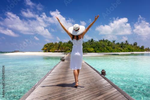 Fototapeta Glückliche Frau in weißem Sommerkleid läuft über einen Holzsteg auf den Maledive