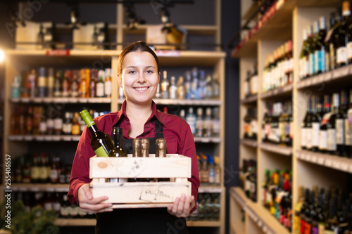 Fotografia  Photo of young brunette seller with wooden box with wine in store