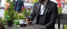 Man In Expensive Custom Tailored Suit Sitting In Coffee Shop And Looking At His Cellphone, Smartphone