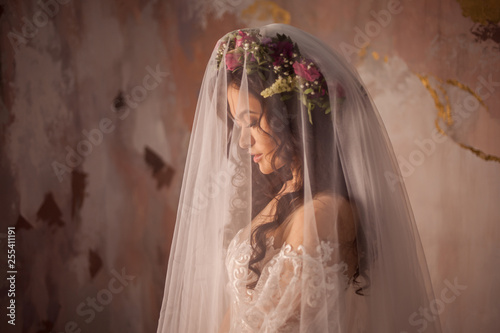 Photo Beautiful young bride in wedding dress with veil on her face