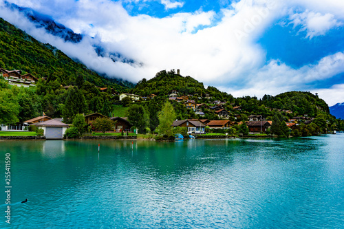 Natural landscape of clear blue lake with mountains and villages in cloudy day