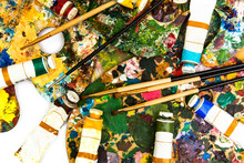 Palette With Colorful Paints. Colorful Oil Painting Palette With A Brush Reaching In. Paint Brushes And Paints For Drawing. Tulip On A White Background