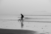 Using A Metal Detector To Search For Hidden Treasure On A Beach At Sunset