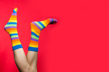 Legs In Funny Socks On Bright Red Background