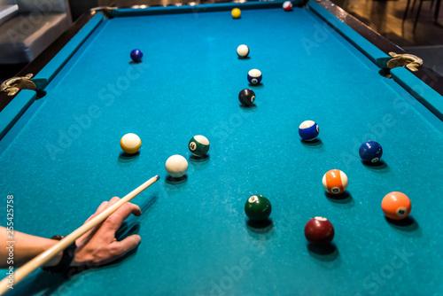 Obraz na plátně Hand with cue aiming on billiard ball at table