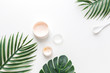 canvas print picture - facial and body spa. face cream on the background of tropical leaves of Monstera palm