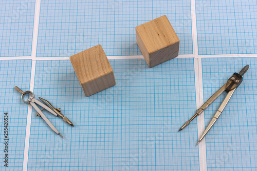 Fotografia  Millimeter paper with draw tools and wooden blocks
