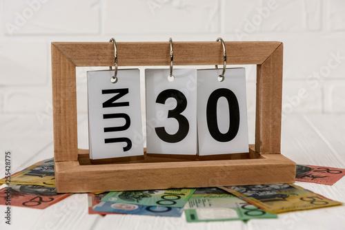 Fotografía  Wooden calendar with australian dollar banknotes closeup