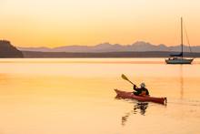 Active, Independent Senior Man Sea Kayaking At Dawn. Outdoor Adventure Water Sports Enjoying Healthy Retirement Lifestyles In Beautiful Nature.