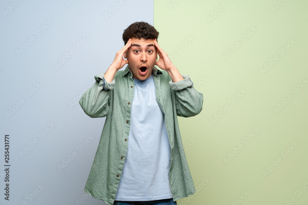 Fototapety, obrazy: Young man over blue and green background with surprise and shocked facial expression