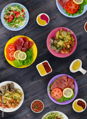 In de dag Eten meat dishes on a plate. salads on a plate. the abundance of food on the table.