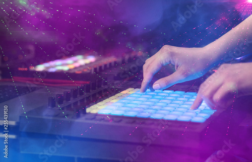 Fotografie, Obraz  Hand mixing music on midi controller with party club colors around