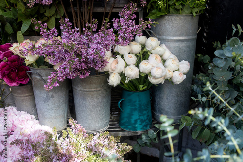 Canvas Print bouquet of lilac and white ranunculus in tin buckets for sale at the entrance to