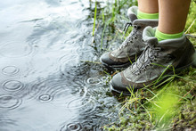 Woman In Tourist Waterproof Hiking Boots Is Standing On The Shore Of A Lake, Right Next To The Water In The Rain.