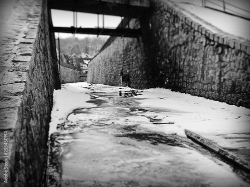 Valokuva  biało czarne zdjęcie zniszczonego roweru który leży pod zaśnieżonym mostem