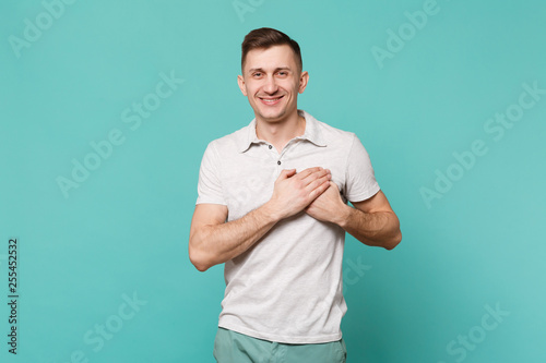 Photo Portrait of pleasant young man in casual clothes standing holding hands on heart, chest isolated on blue turquoise background in studio